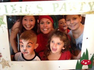 Pixie in a photo frame with children after the end of the party.  Pixie provides Children's Entertainment for London, Surrey, Hertfordshire and the Home Counties.